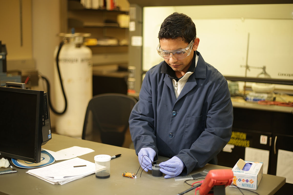 Dilli Dhakal, an OSU-Tulsa student pursuing a master's degree in materials science and engineering, tests the product he created to protect wind turbines and aircraft from lightning damage.