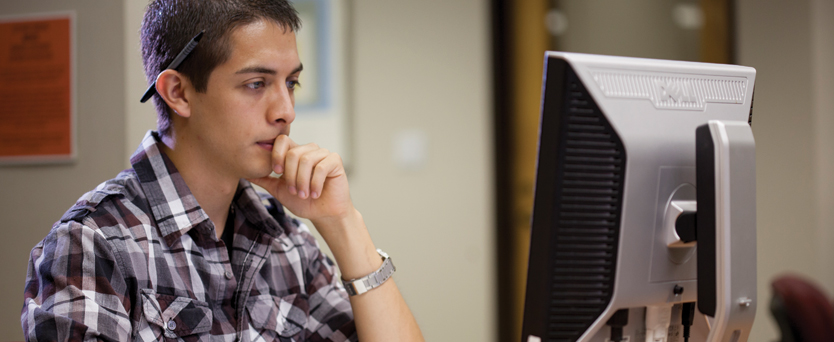 A male student works at a computer