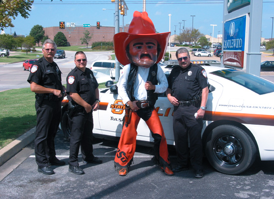 Officer David Pillars, Officer Pat Law and Sgt. Montie Burchett with Pistol Pete at Cops on Doughnut Shops benefitting the Special Olympics.
