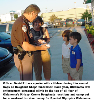 Officer David Pillars speaks with children during the annual Cops on Doughnut Shops fundraiser