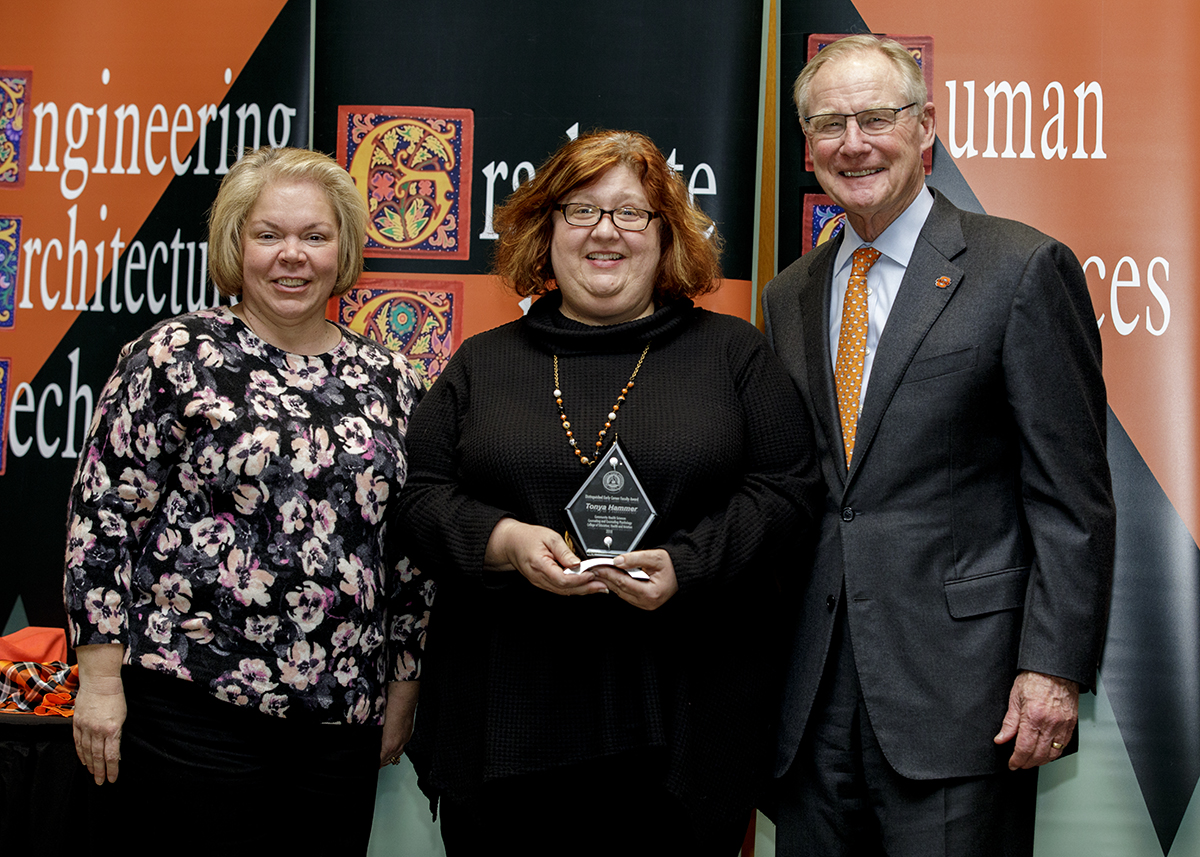 Dr. Tonya Hammer, associate professor in counseling and counseling psychology, center, was presented the 2018 Distinguished Early Career Faculty Award by OSU President Burns Hargis and Dr. Mindy McCann, OSU Faculty Council chair and professor of statistics.