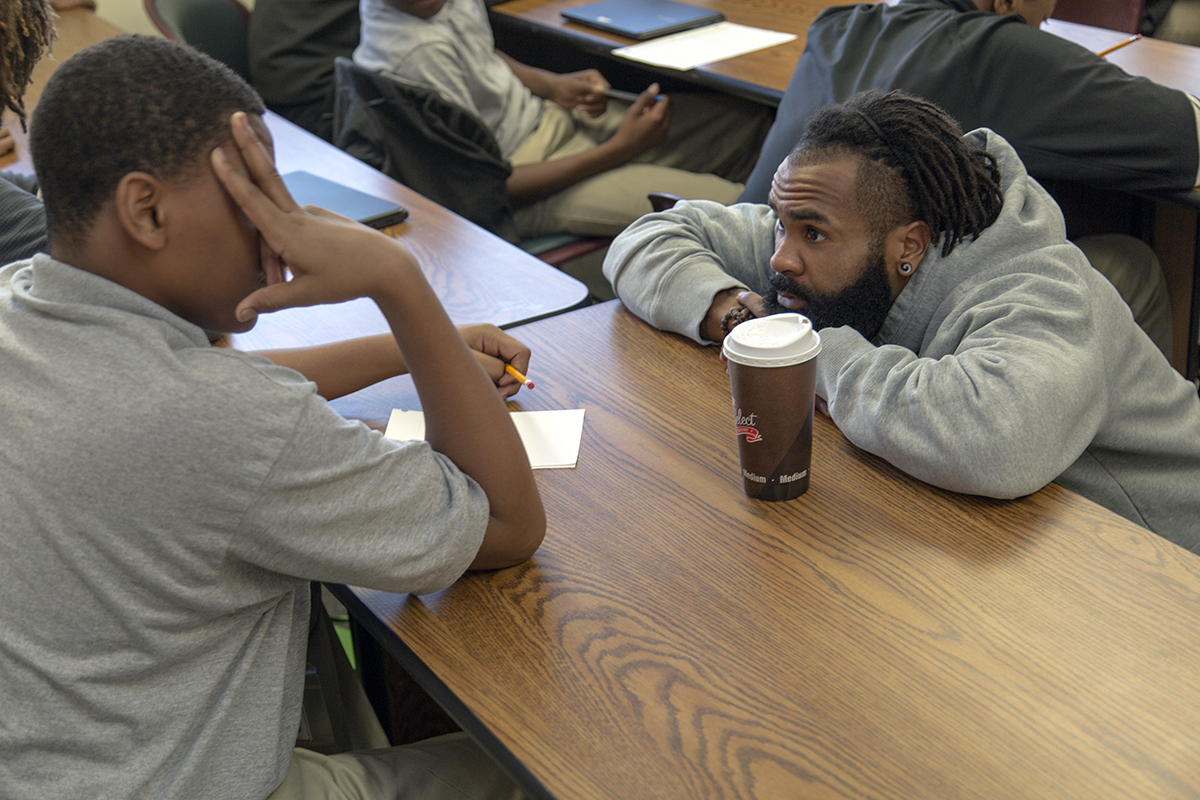 RJ Young discusses writing with a ninth-grade student at KIPP Tulsa College Preparatory School.