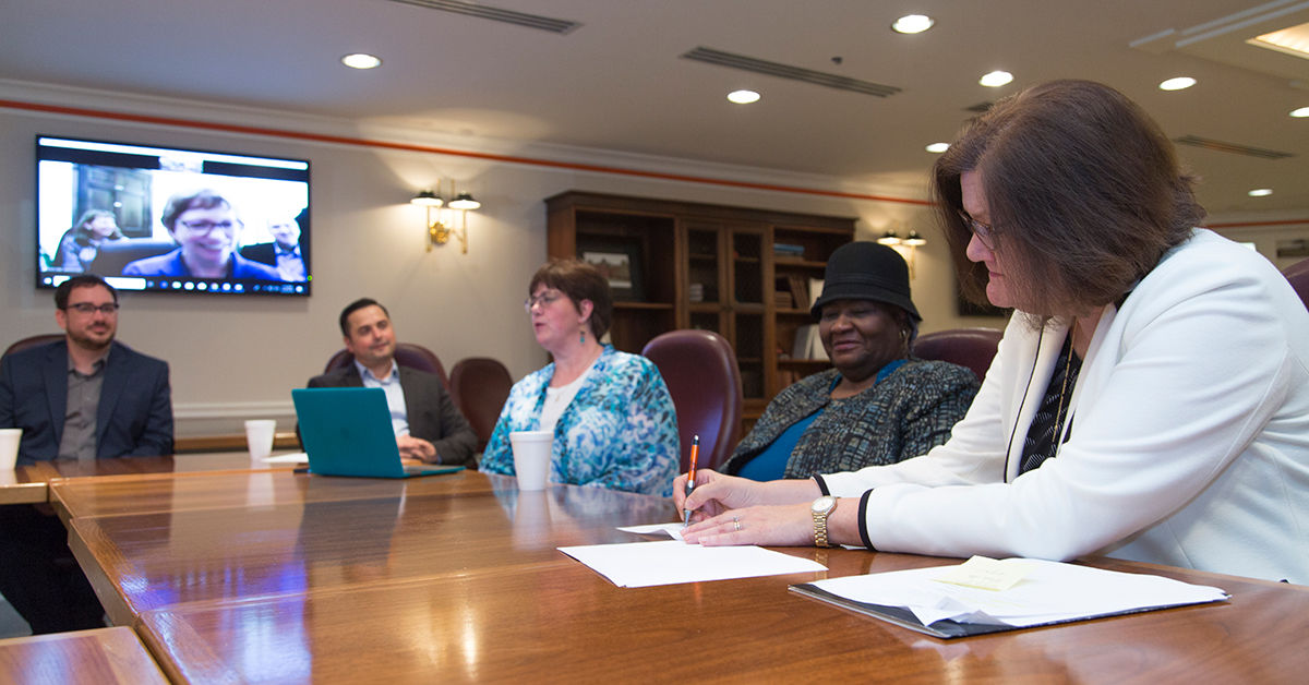 President Pamela Fry, right, signs the memorandum of understanding making OSU-Tulsa an anchor partner for Everyday Democracy with Nelda English, Dr. Tami Moore, Dr. Mike Stout and Patrick Grayshaw. Martha McCoy, executive director of Everyday Democracy, is on screen as part of the virtual signing.