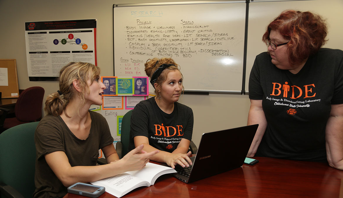 Doctoral students Ashley Hadwiger (left) and Jennie Martin discuss a research project with Dr. Tonya Hammer in the Body Image and Disordered Eating (BIDE) Lab at OSU-Tulsa