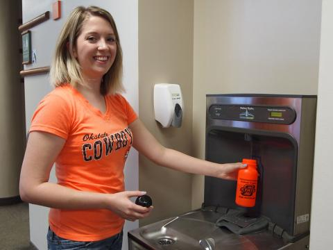Graduate student Lauren Branum fills a reusable water bottle to help reduce waste at the OSU-Tulsa campus.