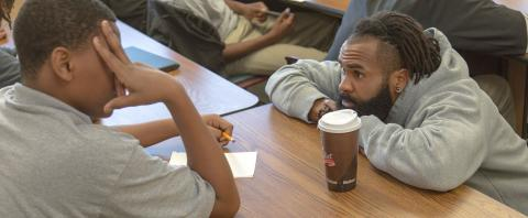 Author and teaching artist RJ Young works with KIPP Tulsa Preparatory student on creative writing