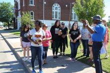 Dr. Shanedra Nowell and workshop participants listen to Dr. Dewayne Dickens during a walking tour of the Greenwood District