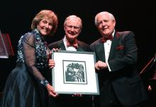 Ann and Burns Hargis, along with Oklahoma State Regent for Higher Education Jay Helm, hold up an original artwork by Native American artist Ben Harjo, gifted to the Hargises at the A Stately Affair gala.