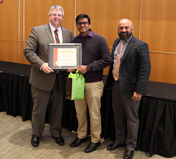 Paul Tikalsky, dean of the OSU College of Engineering, Architecture and Technology, left, presents Vishal Yeddu, a master's student in materials science and engineering, the college's top graduate award at the recent awards banquet in Stillwater, along with Dr. Raman Singh, head of the School of Materials Science and Engineering at OSU-Tulsa.